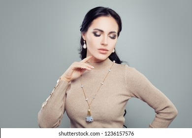 Pretty brunette woman in jewelry gold earrings with diamond and pearls and necklace