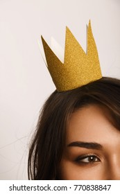 Pretty brunette woman looking away and posing with paper-made crown on head.