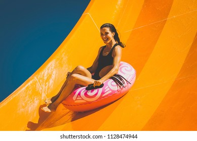 pretty brunette woman on the inflatable ring having fun on the orange water slide in the aqua park. Summer Vacation. Weekend on resort