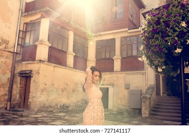 Pretty brunette woman posing at the courtyard in rays of sun. Vintage toning effect