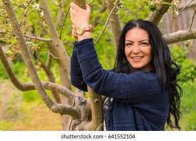 Pretty brunette woman posing in garden in sunny day
