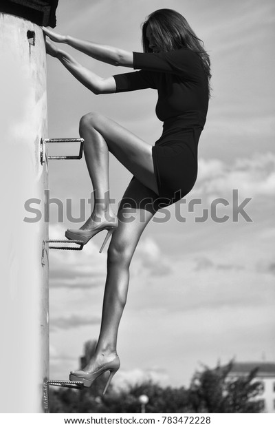 Pretty brunette woman in red dress with high beige heels climbs to roof on blue sky outdoor