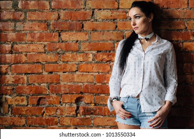 Pretty brunette woman in shirt and denim shorts standing near brick wall.
