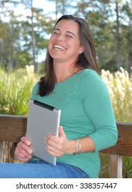 A pretty brunette woman sitting on a wooden park bench laughing while holding a wireless device. She is very happy. She is wearing a green shirt and blue jeans. Vertical composition.
