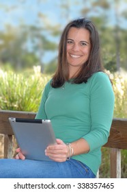 A pretty brunette woman sitting on a wooden park bench in a natural setting. She is wearing a green shirt. She is smiling pleasantly at the viewer. Vertical image with copy space left.