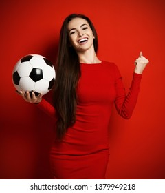 Pretty brunette woman in tight red dress with soccer ball in her hand on her palm is ready to dance with happiness celebrate a win on red background