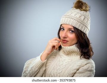 Pretty brunette woman in warm winter fashion wearing a woollen cap and matching cable-knit polo neck sweater turning to look at the camera with a smile, head and shoulders on grey with copy space