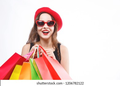Pretty brunette woman wearing black dress, red cap and sunglasses holding many colorful shopping bags and laughing on the white background, concept of consumerism, sale, rich life