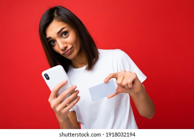 Pretty brunette woman wearing everyday stylish white t-shirt isolated on red background wall holding and using phone and credit card making payment looking at camera and having questions