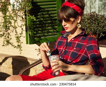 Pretty brunette woman wearing red skirt, checked shirt, band, aviator sunglasses, resting in a wickered chair in a street cafe, drinking her cold milk shake cocktail. On a hot summer day