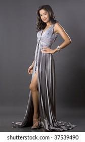 pretty brunette woman wearing silver dress on grey