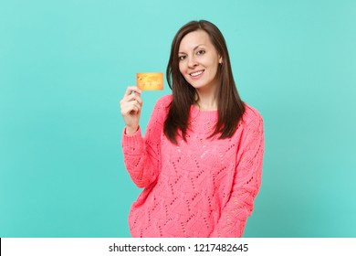 Pretty brunette young woman in knitted pink sweater looking camera holding in hand credit card isolated on blue turquoise wall background studio portrait. People lifestyle concept. Mock up copy space