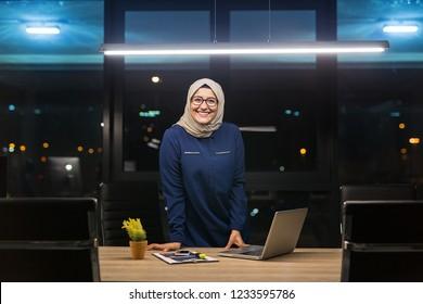 Pretty business hijab woman working alone in dark office