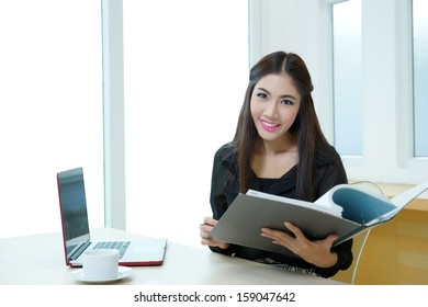 Pretty business lady working at desk, Model is Asian woman.