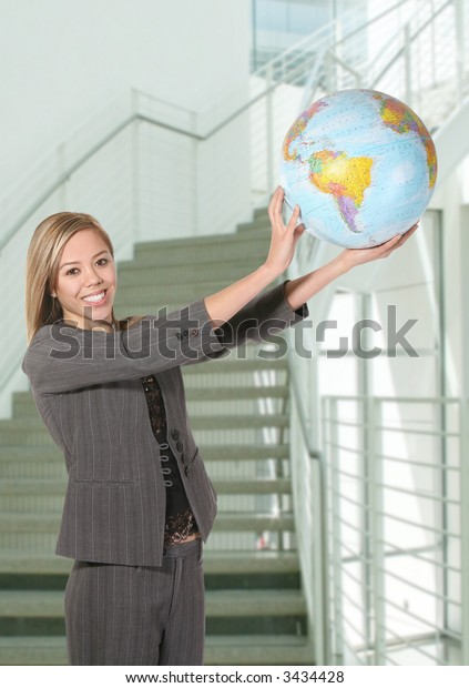 A pretty business woman holding the globe in the sky