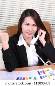 pretty business woman sitting at her desk talking on the telephone