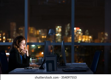 Pretty business woman working alone in dark office