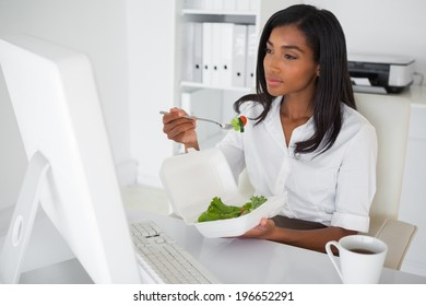 Pretty businesswoman eating a salad at her desk in her office