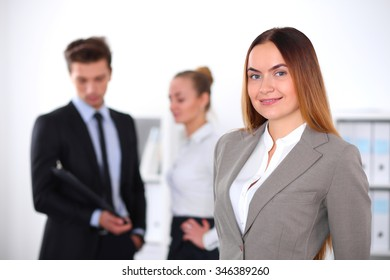 Pretty businesswoman in office with colleagues in the background