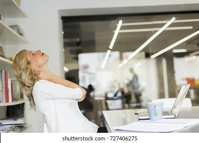 Pretty businesswoman in the office taking a break and doing a neck exercise