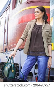 pretty businesswoman on vacation at the railway station near the passenger railcar in anticipation of a trip