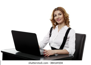 Pretty businesswoman sitting at her desk, using a laptop