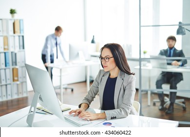 Pretty businesswoman sitting at her desk and typing on computer