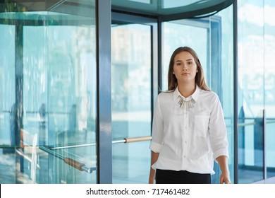 Pretty businesswoman standing in front of revolving door