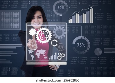 Pretty businesswoman using a virtual screen to operate business gear with financial background