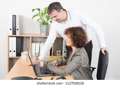 pretty businesswoman work at office desk with businessman boss on computer