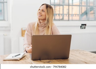 Pretty businesswoman working on a laptop turning to the side with a warm smile as she watches something
