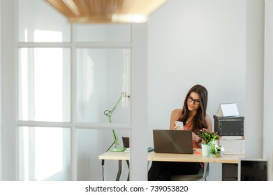 Pretty busy woman sitting at home desk working on laptop computer and using mobile phone.