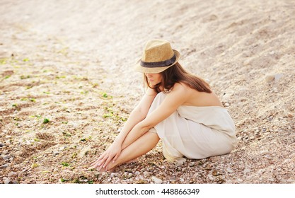 Pretty calm woman relax sitting alone on a sand beach, dressed in white dress and hat