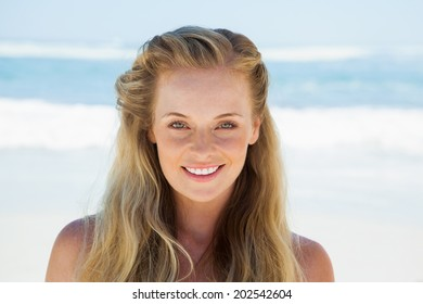 Pretty carefree blonde smiling at camera on the beach on a sunny day