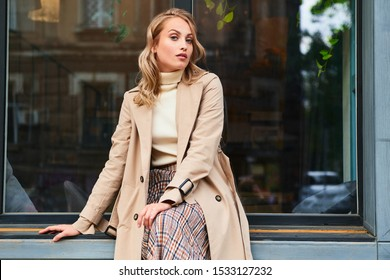 Pretty casual blond girl in stylish trench coat confidently looking in camera on city street