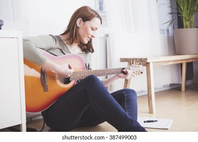 Pretty casual dressed woman with long brown hair sitting on the floor of the living room playing some records on guitar