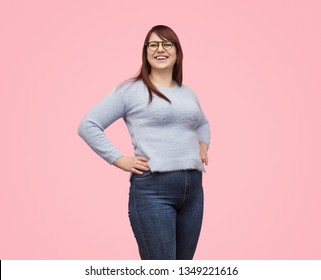Pretty casual woman of plus-size wearing sweater with jeans and laughing on pink background