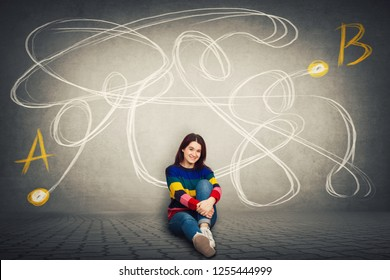 Pretty casual woman sitting on the floor finding the correct way from point A to point B. Solving problem, find solution, business idea and creativity concept.