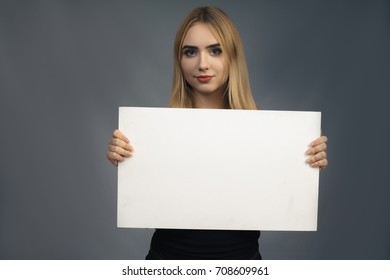 Pretty casual young woman with a blank white sign or placard in her hand pointing at it as she looks down with a smile, isolated on grey