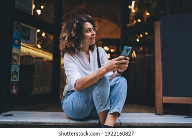 Pretty Caucaisan woman with modern cellphone device in hands resting at touristic street sitting outdoors and smiling, charming hipster girl holding smartphone technology for network and looking away - Shutterstock ID 1922160827