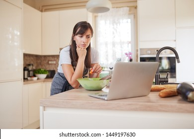Pretty Caucasian brunette in apron leaning on kitchen counter and looking at laptop and following recipe for dinner. Woman holding carrot in hand.