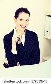 Pretty caucasian businesswoman sitting in the office holding keys.