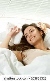 Pretty Caucasian female lying in bed on a light background