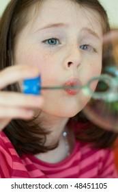 Pretty caucasian girl blows soap bubbles