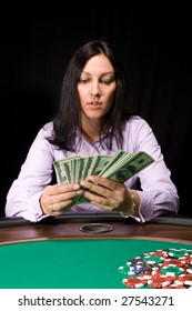 Pretty caucasian girl in the casino takes cash over green felt