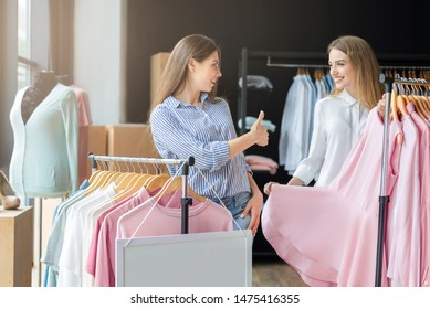 Pretty Caucasian Girl Endorsing Her Girlfriend Choise With Thumb Up In Boutique, elegant pink dress, copy space