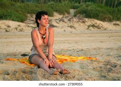 Pretty caucasian girl on the yellow sand over colorful sunset in Goa