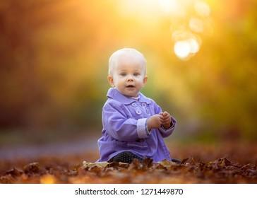 Pretty caucasian kid in autumnal landscape. Happy child in nature.