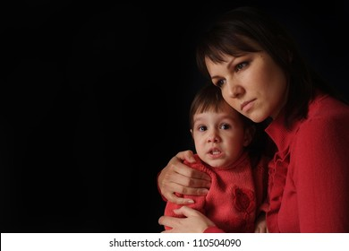 A pretty Caucasian mama with a sad crying daughter on a dark background