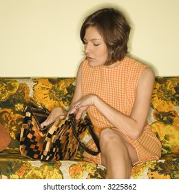 Pretty Caucasian mid-adult woman sitting on colorful retro sofa searching in handbag.